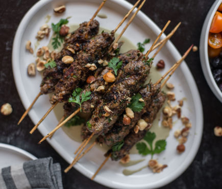 cooked hazelnut lamb kabobs on a plate with garnish